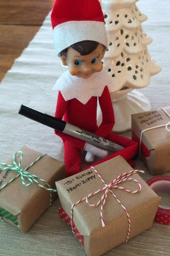elf on the shelf idea wrapping presents with pen in his hands