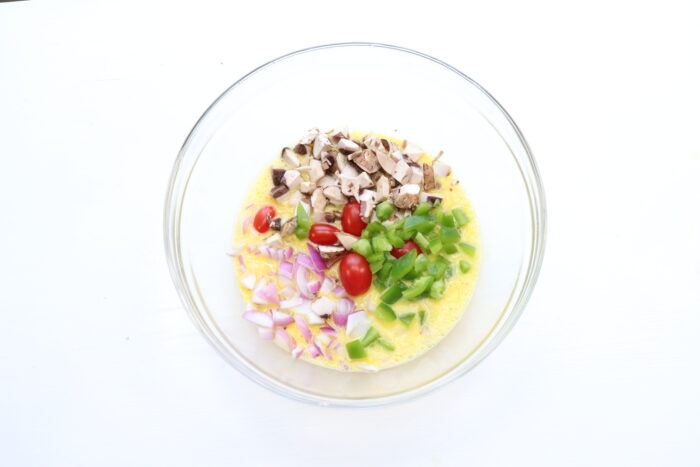 Eggs and veggies in glass bowl for Weight Watchers breakfast casserole