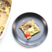 Slice of breakfast casserole on black plate next to dish