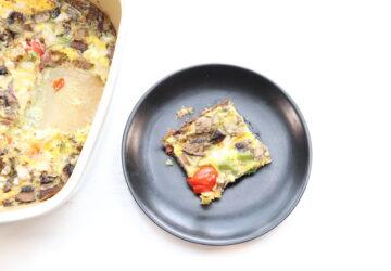 Slice of breakfast casserole on black plate next to dish