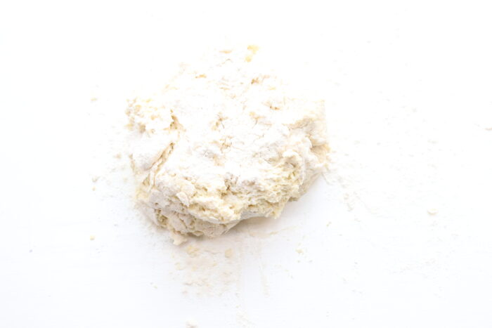 Dough needed into a ball on white counter