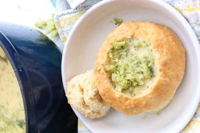 Broccoli soup in bread bowl on white plate