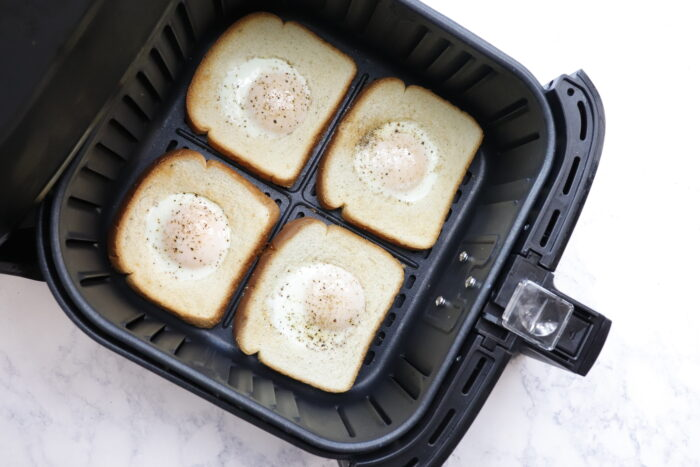 Air fryer eggs in a basket one side cooked