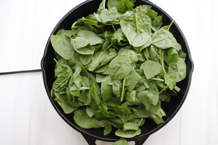 spinach in black pan on stove
