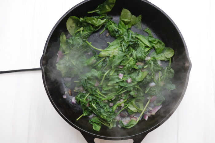 Spinach and onions in black pan after cooking