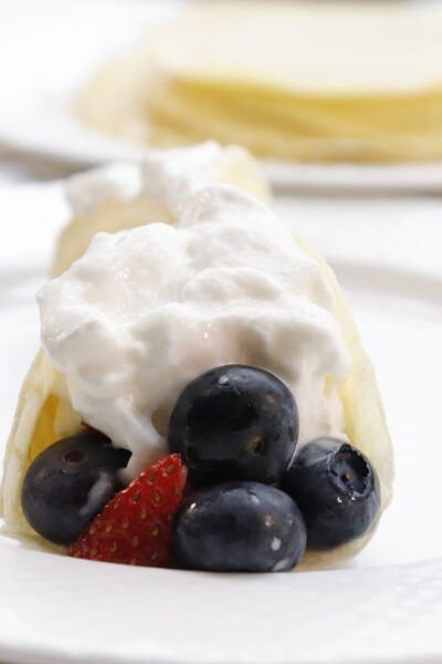 front view of breakfast crepes with berries topped with cool whip