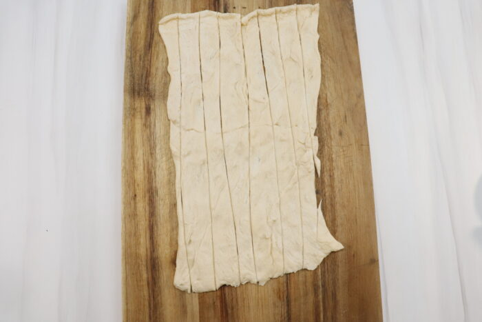 dough cut into strips on wooden cutting board