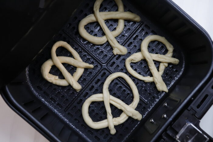4 folded pretzels in air fryer basket