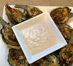roasted artichokes with remoulade on white plate | Slap Dash Mom