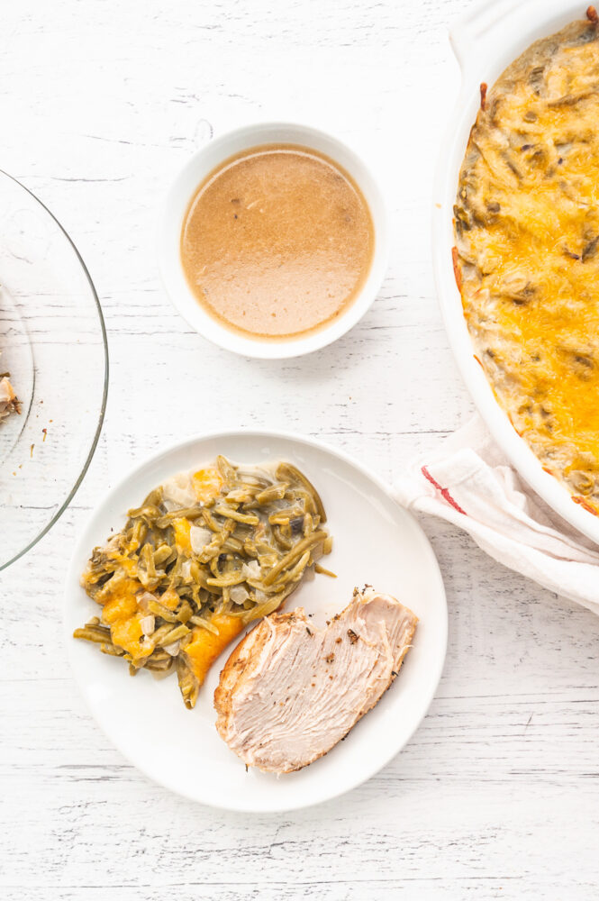 Instant pot turkey breast next to green bean casserole and gravy