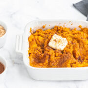 close up of Instant pot mashed sweet potatoes in a casserole dish topped with butter