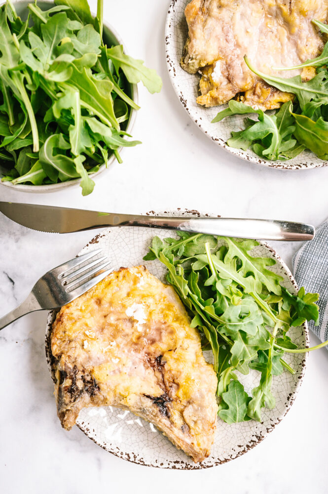 air fryer pork chops with silverware and salad