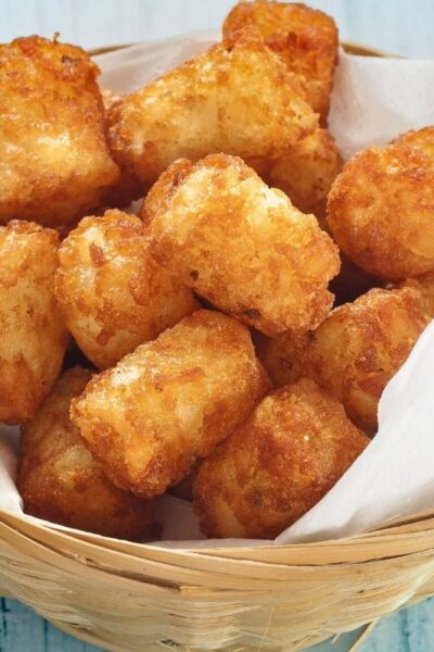 air fryer tater tots in a basket with parchment paper