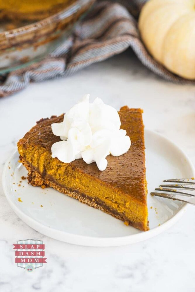 slice of pumpkin pie made with coconut milk on a white plate topped with whip cream