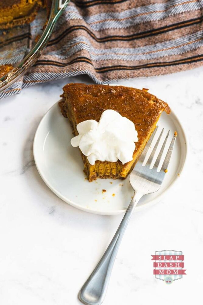 pumpkin pie on a white plate next to a fork with a bite taken out