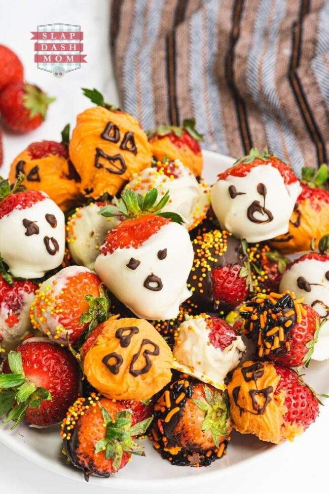 chocolate covered strawberries with while chocolate and milk chocolate that look like ghosts and jack o lanterns