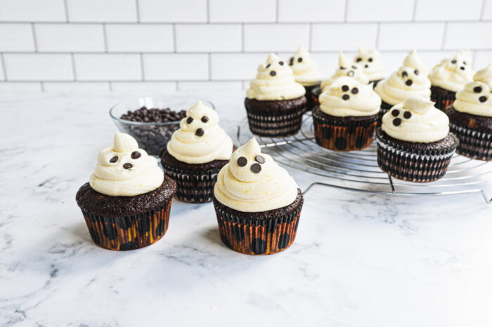 ghost cupcakes after baking next to bowl of chocolate chips