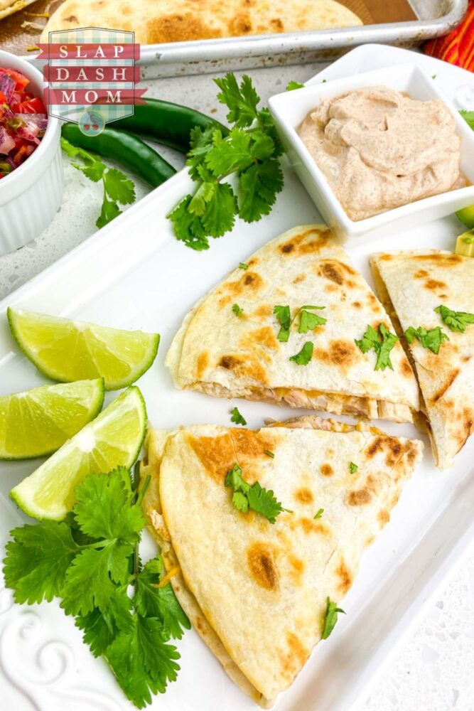 air fryer chicken quesadillas on white plate next to sauce and lime wedges