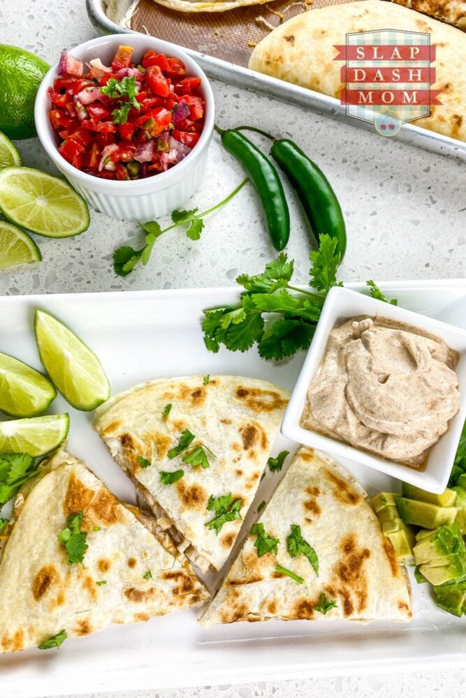 top shot of chicken quesadillas cut in triangles on white plate near salsa