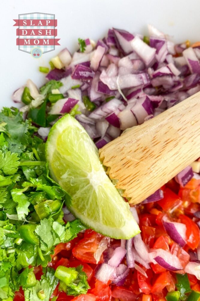 ingredients for pico de gallo in bowl with lime wedge