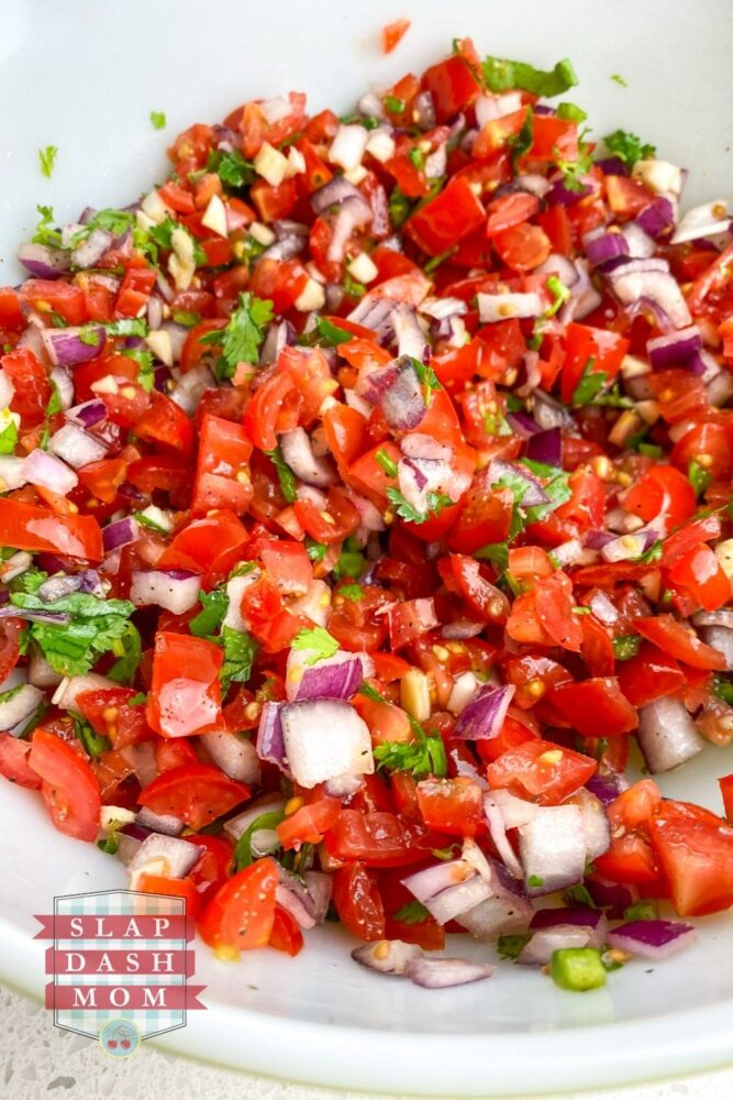 ingredients mixed together in white bowl for pico de gallo without jalapenos