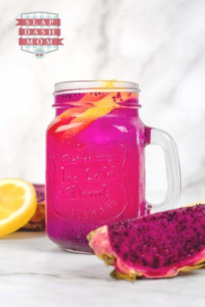 dragon fruit lemonade in a mason jar with handle next to cut dragon fruit