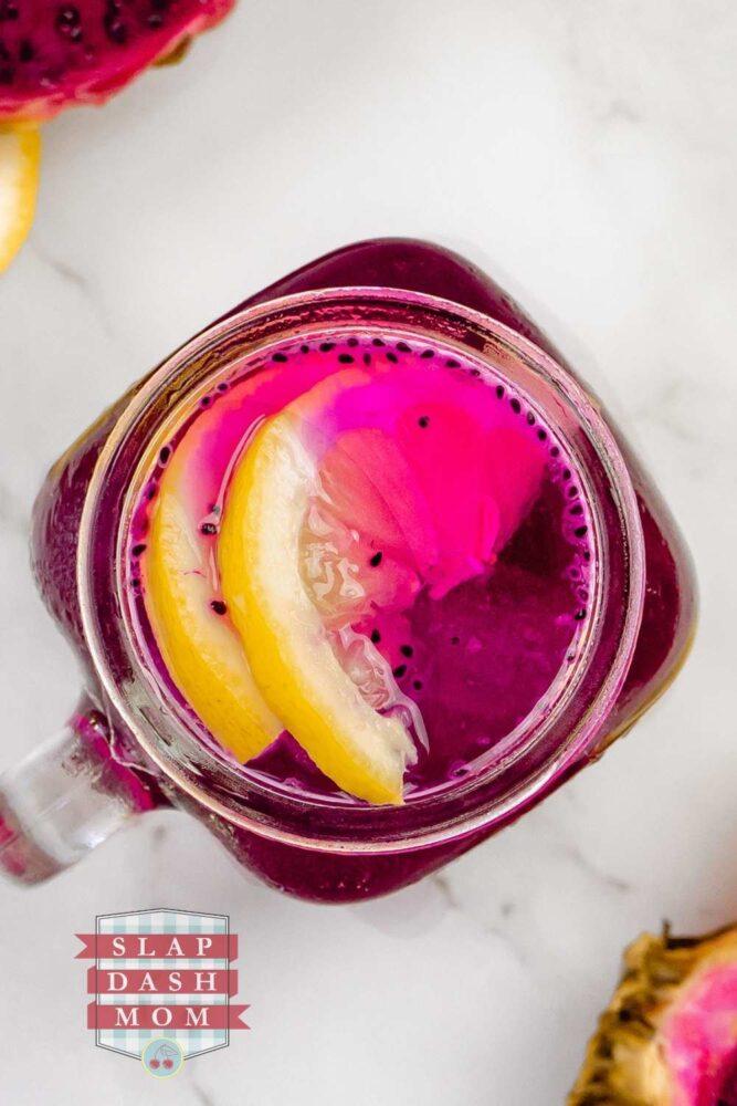 top shot of dragon fruit lemonade with lemons in the glass