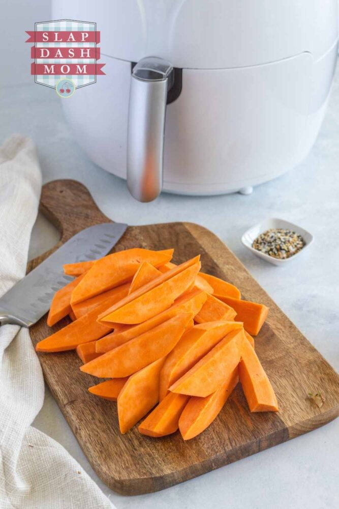 sweet potato wedges on cutting board with air fryer in the background