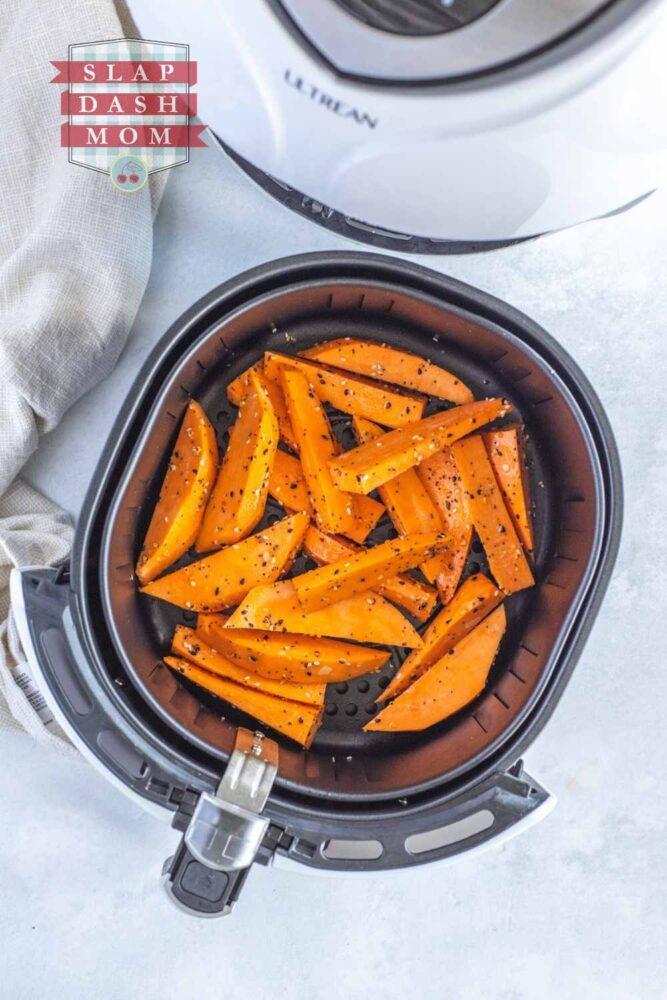 top shot of sweet potato wedges with seasoning in air fryer basket