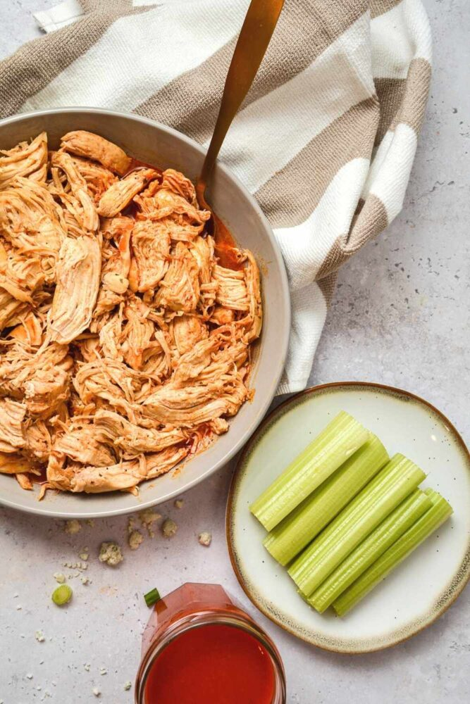 buffalo chicken made in the instant pot in a bowl with a spoon