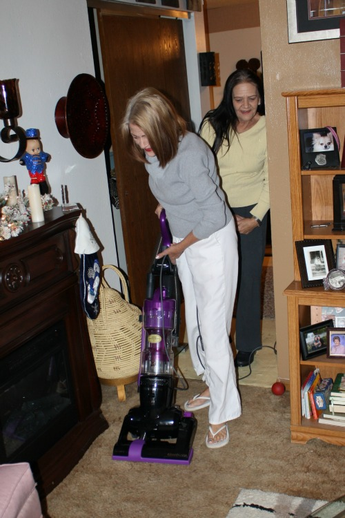 mom kisses her son when she was vacuuming